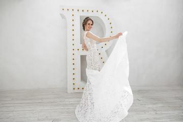 Beautiful bride posing in wedding dress in a white photo Studio. Mirror. Sofa. Bouquet. The door. Chandelier.