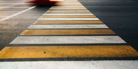Yellow and white lines on the asphalt road, pedestrian crossing. The concept of road safety.