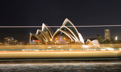 Bats can be seen flying over the top of the Sydney Opera House while a ferry passes by in front during a long exposure on the Sydney Harbour
