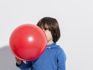 5 year old boy blowing a red balloon