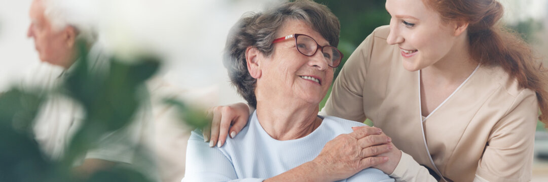 Caregiver comforting smiling senior woman