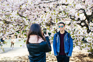 Woman taking a portrait of his friend in front of a cherry tree.