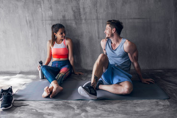Man and Woman in Sportswear Sitting on the Floor and Chatting