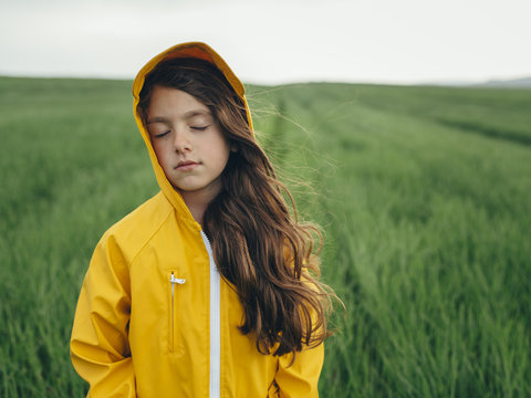 Close up of girl with eyes closed standing in wheat field