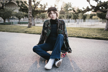 young woman sitting on skateboard in park at sunset