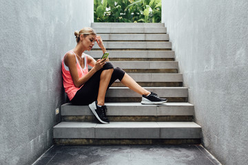 Pretty Fitness Woman Using Her Phone After Workout
