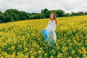 Beautiful girl in a dress among yellow flowers in a field