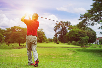 Man playing golf on a golf course in the sun