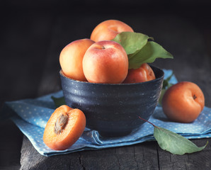 Apricots. Closeup of fresh organic apricot fruits in a bowl on dark rustic wooden table