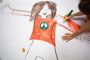 Girl sitting colouring in body trace outline