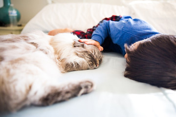 Young boy stroking cat lying on bed