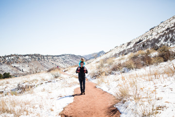 Father with daughter on shoulders on hiking trail