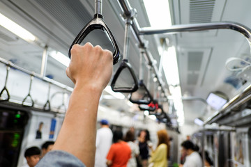 hand holding onto a subway train handle