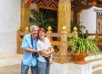 Smiling happy couple standing near the entrance of a temple at Thimphu, Bhutan.