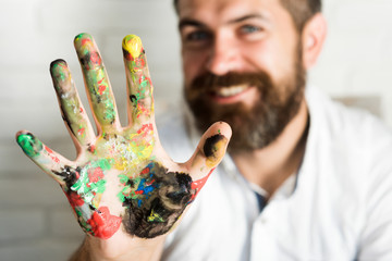 Colorful man hand. Bearded handsome man shows palm with paints, smiles in camera, happiness art, happy young artist, hand in paint, drawing teacher draw with fingers picture. Yellow, red, green colors