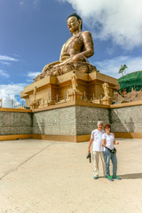 Couple smiling near  giant Buddha Dordenma statue with the blue sky and clouds background, Thimphu, Bhutan
