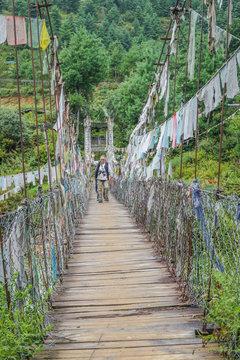 People walking on Bhutanese pedestrian suspension bridge with prayer flags in greenery area, Bhutan.