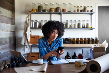 Millennial African American Woman businesswoman texting in her skincare studio