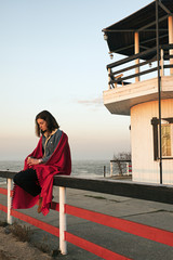 Sad girl in red blanket with hot drink against of light house