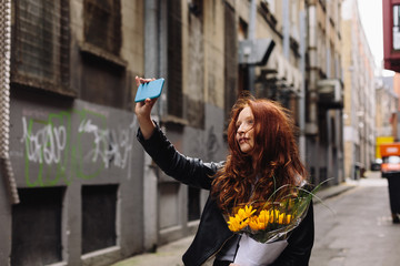 Young Beautiful Woman Taking a Self Portrait Holding Flowers after a Date
