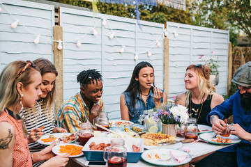 Group of young people having lunch and soft drinks in a garden party