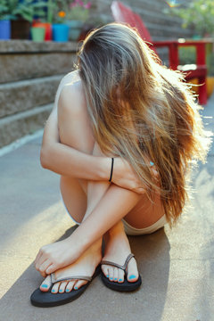Teenage girl hiding behind her long, blonde hair