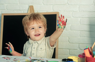 Paint fingers, boy draws with hands and shows multi-colored palm. Education and development, art drawing, children's educational games with paints and paper. Home alternative education without school