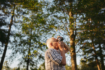Old senior man taking pictures with old slr film camera