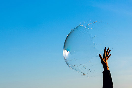 Hand reaching up to pop a big bubble