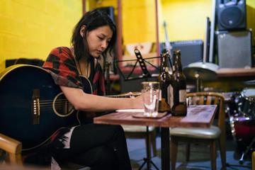 Asian woman playing the guitar