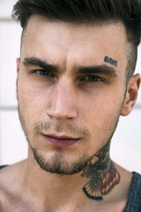 Close-up of serious young tattooed man looking at camera