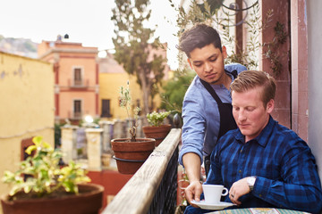 Waiter serving young man a cup of coffee