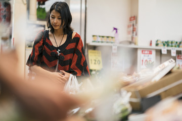 Young asian woman buying vegetables