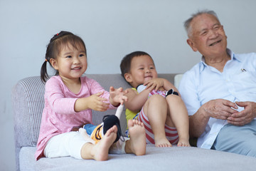happy senior asian man having fun with his two great granddaughter indoor