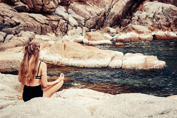 Young woman sitting back, meditate in lotus yoga pose outdoor, on the beach
