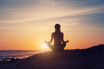 silhouette of Young woman sitting back, meditate in lotus yoga pose outdoor, on the beach