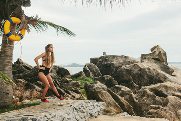 Young sport style female doing exercise outdoor on sea shore