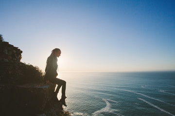 Silhouette of Woman wearing dreadlock sitting on cliff outdoor and looking to Atlantic Ocean