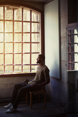 Young man with beard and dark skin sitting near cell window