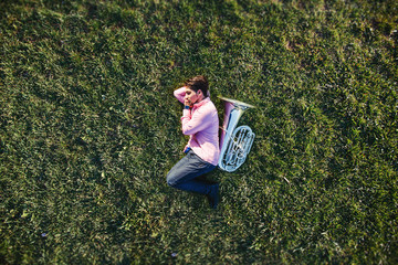 Musician lying on grass field hugging his musical instrument tuba