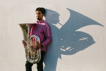 Portrait and shadow of Musician with his musical instrument tuba. White wall background