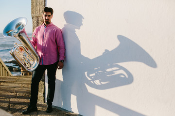 Outdoor Portrait of musician with tuba wind musical instrument. Shadow, white backgroung