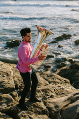 Outdoor Portrait of musician with tuba wind musical instrument. Sea shore, Atlantic Ocean