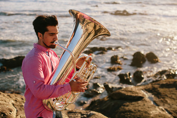 Outdoor Portrait of musician with tuba wind musical instrument. Sea shore, Atlantic Ocean