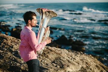 Young man playing on Tuba on rocky sea coast