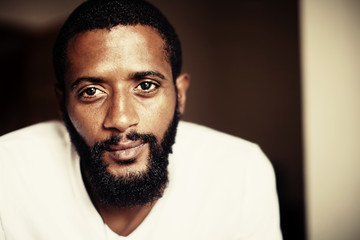 Portrait of handsome man with beard. Mixed race black skin