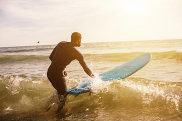 Man going to surfing, walking to ocean. Mixed race black skin and beard
