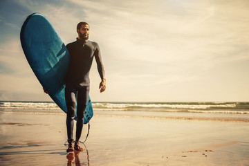 Portrait of surfer man with surf board on the beach. Mixed race black skin and beard. Summer sport activity