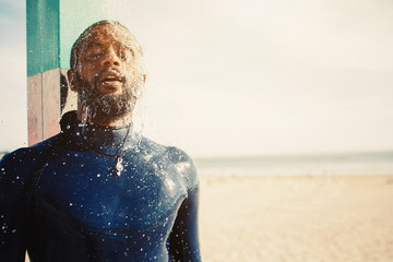 Portrait surfer man taking a shower on the beach. Mixed race black skin and beard. Summer sport activity