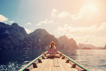 Young female sitting on the boat in yoga lotus pose and meditate. Travel on mountain lake, Thailand